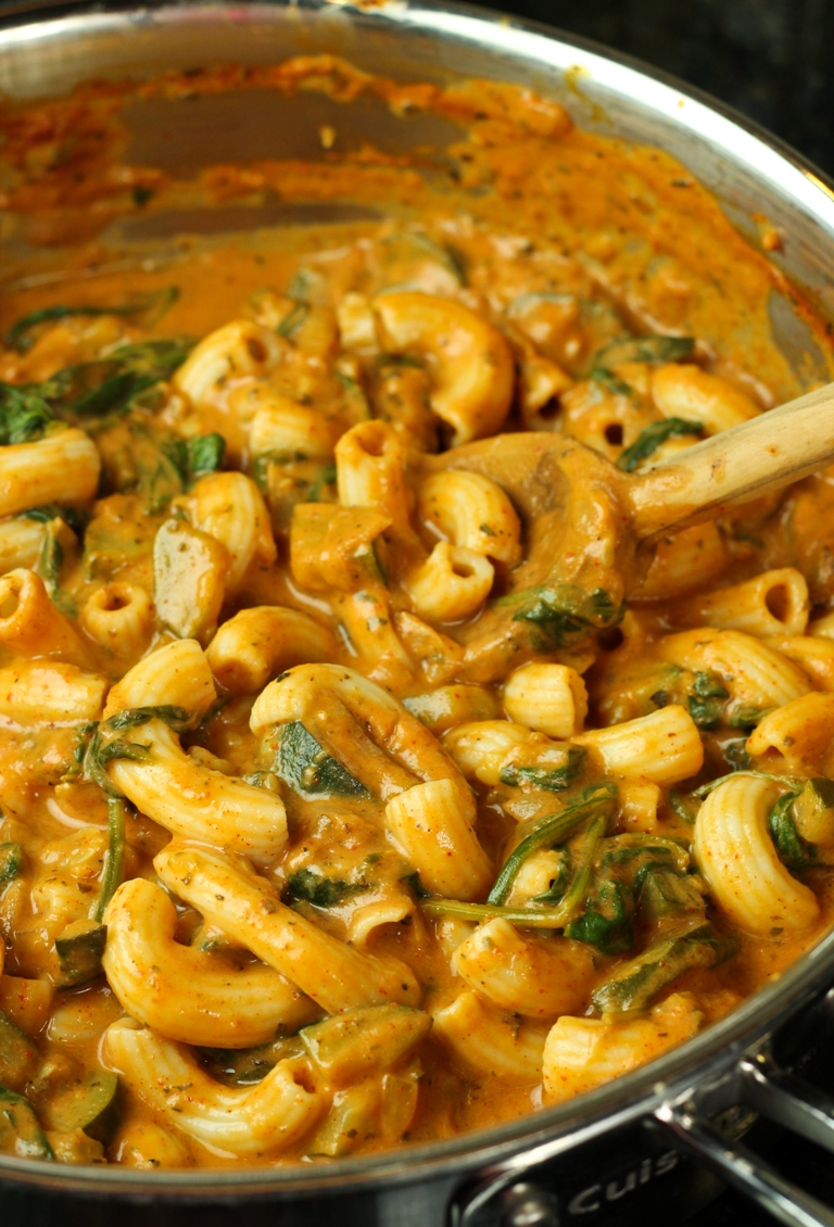 Closeup view of stirring pasta in creamy chili sauce