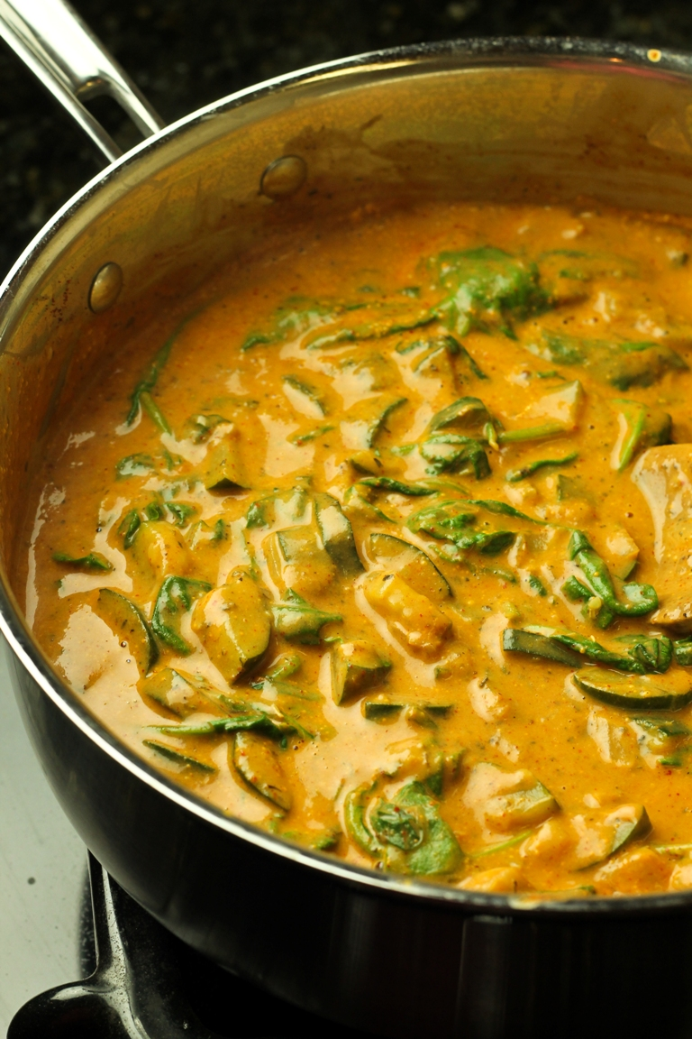 Cooking Creamy Chili Sauce with Zucchini and Spinach in pan on stove