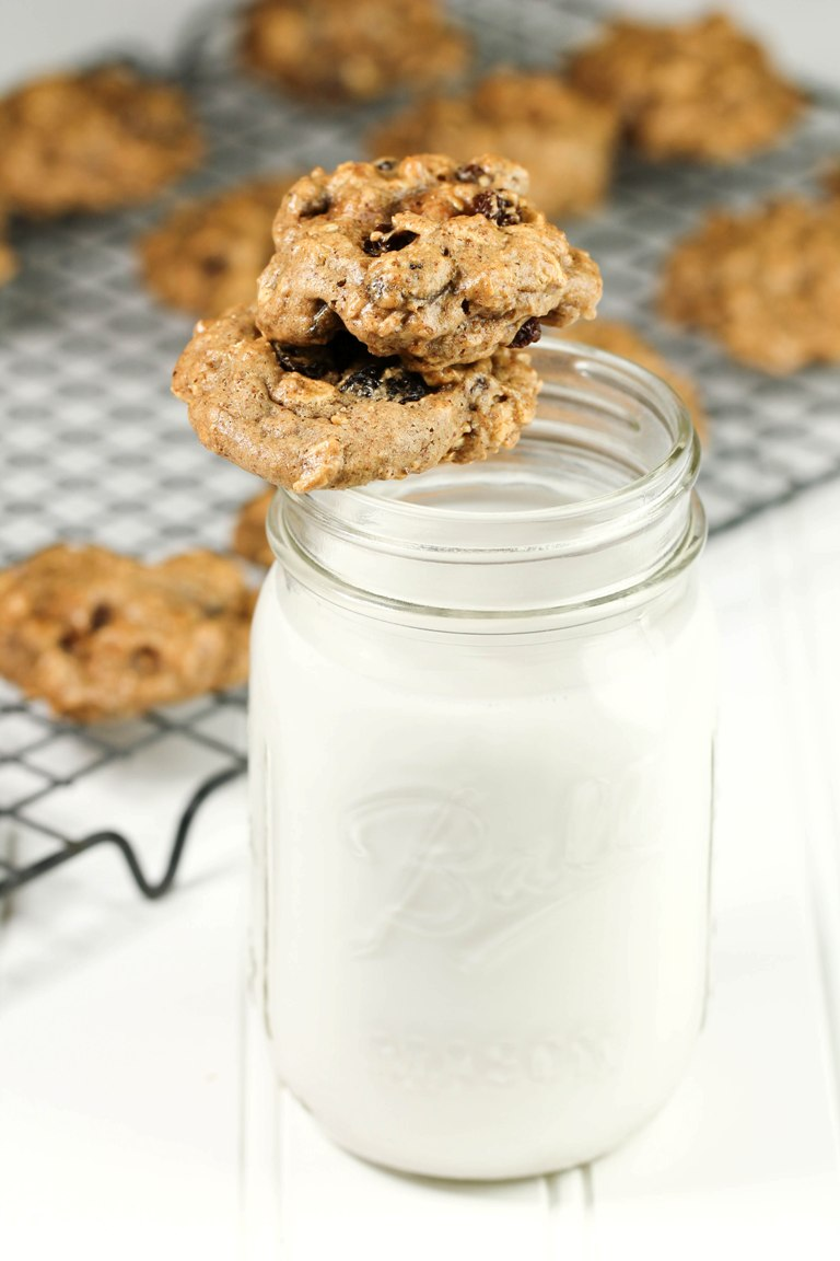 Glass of milk with vegan oatmeal raisin cookies on top