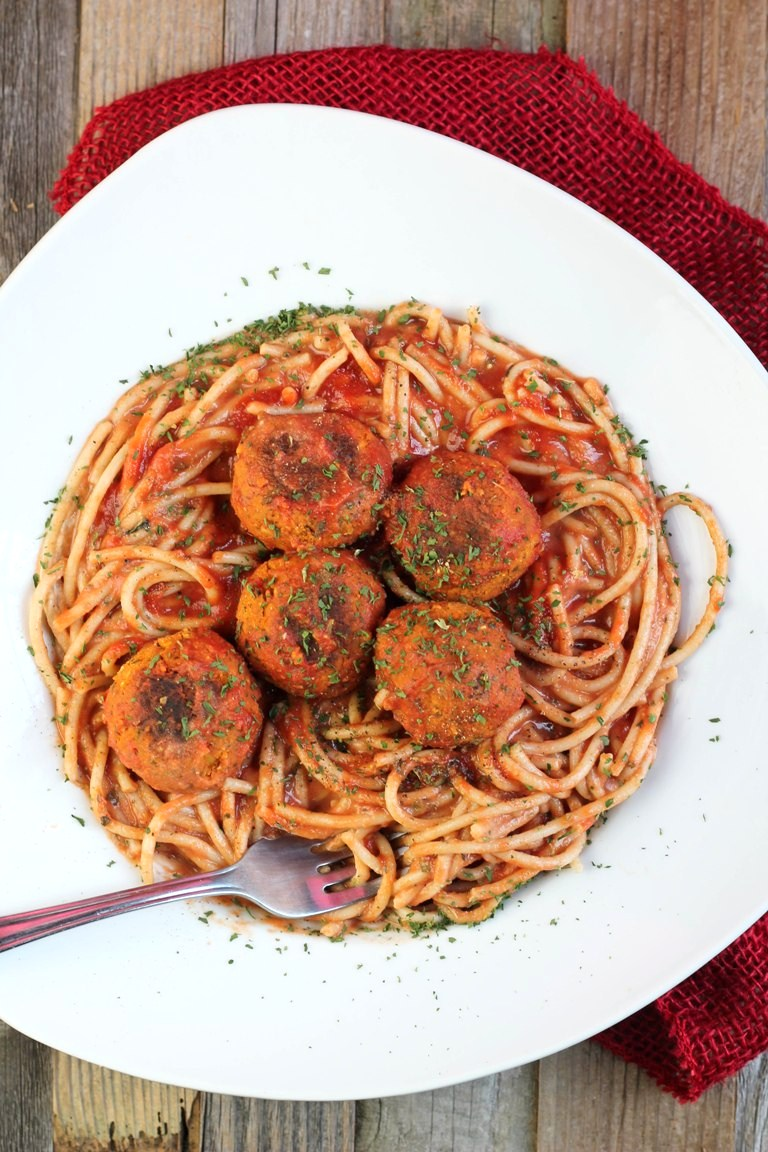 Overhead view of white bowl of vegan meatballs and spaghetti