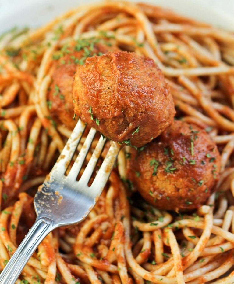Fork holding up vegan meatball over spaghetti