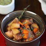 vegan stew in brown bowl with fresh thyme
