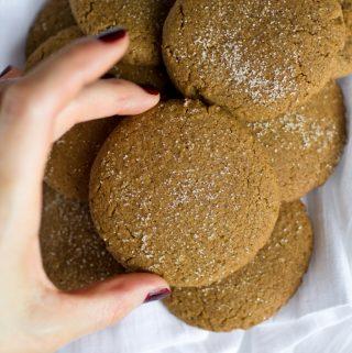 hand grabbing vegan gingersnap cookie from bowl