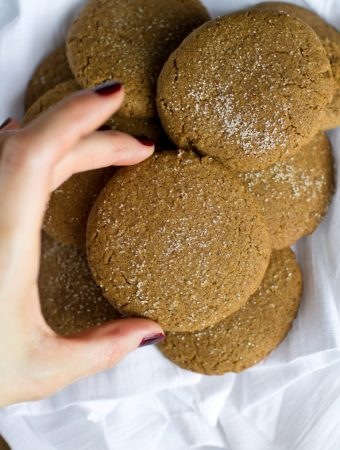 hand grabbing vegan gingersnap cookie from bowl