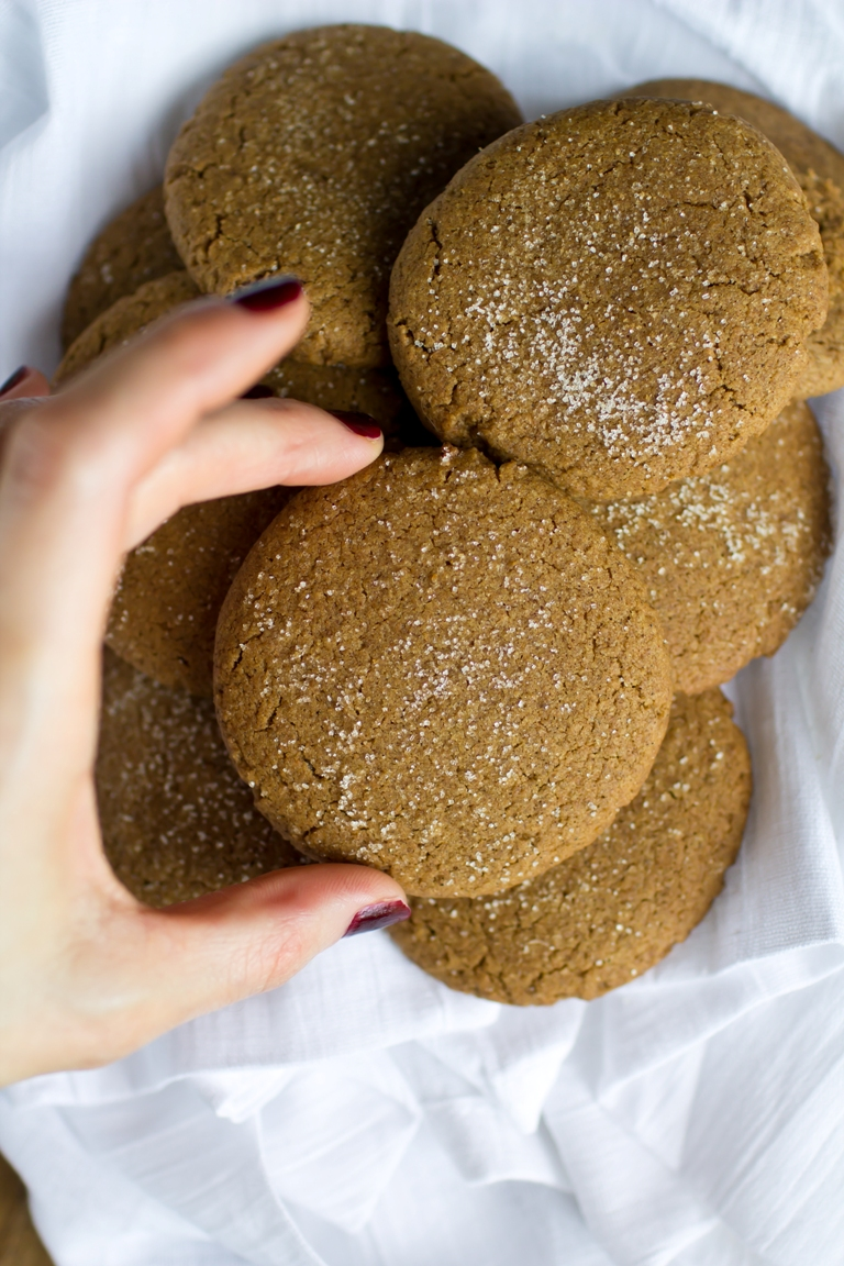 lady's hand grabbing vegan gingersnap cookie from stack