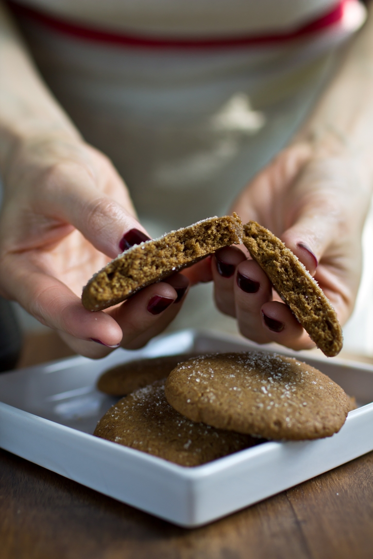 Hands breaking a vegan gingersnap cookie
