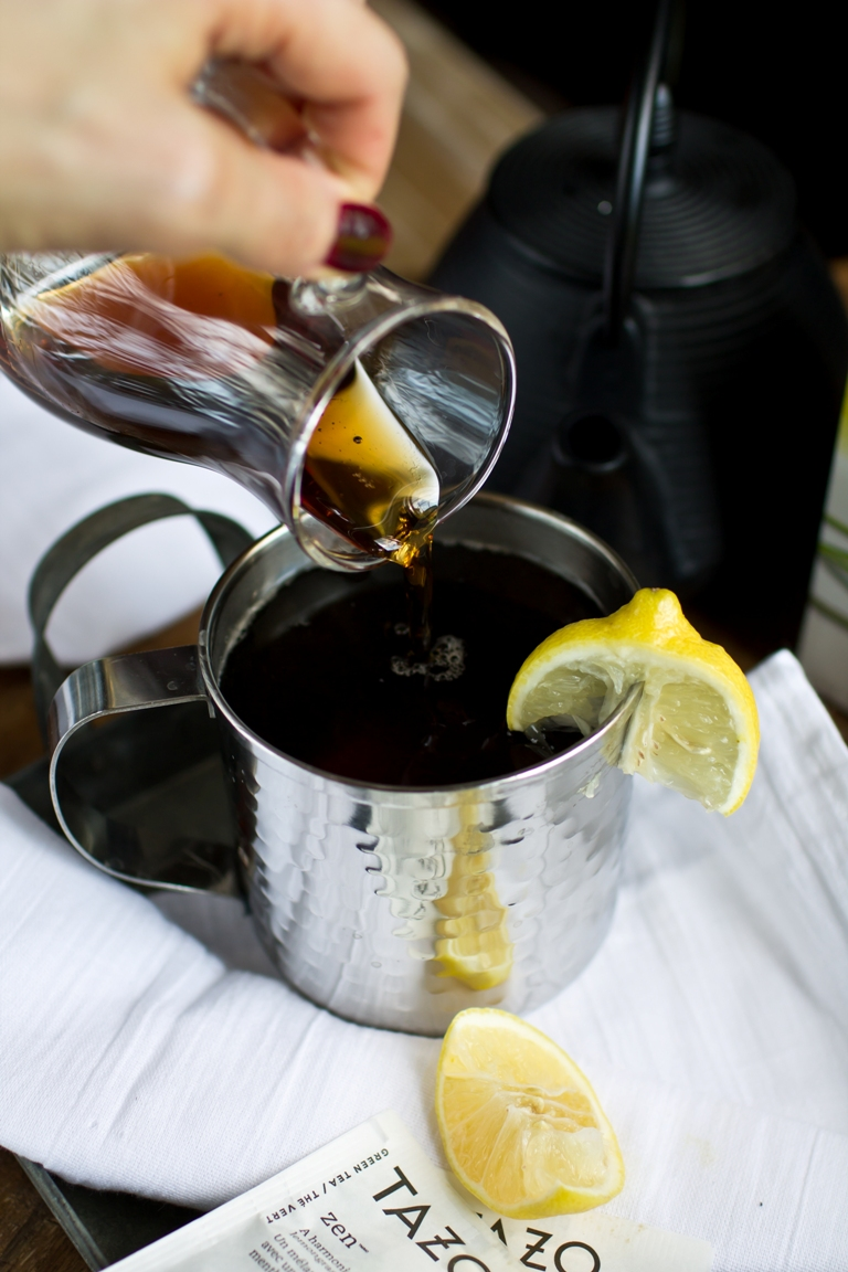 glass of syrup being poured into mug of tea with lemon