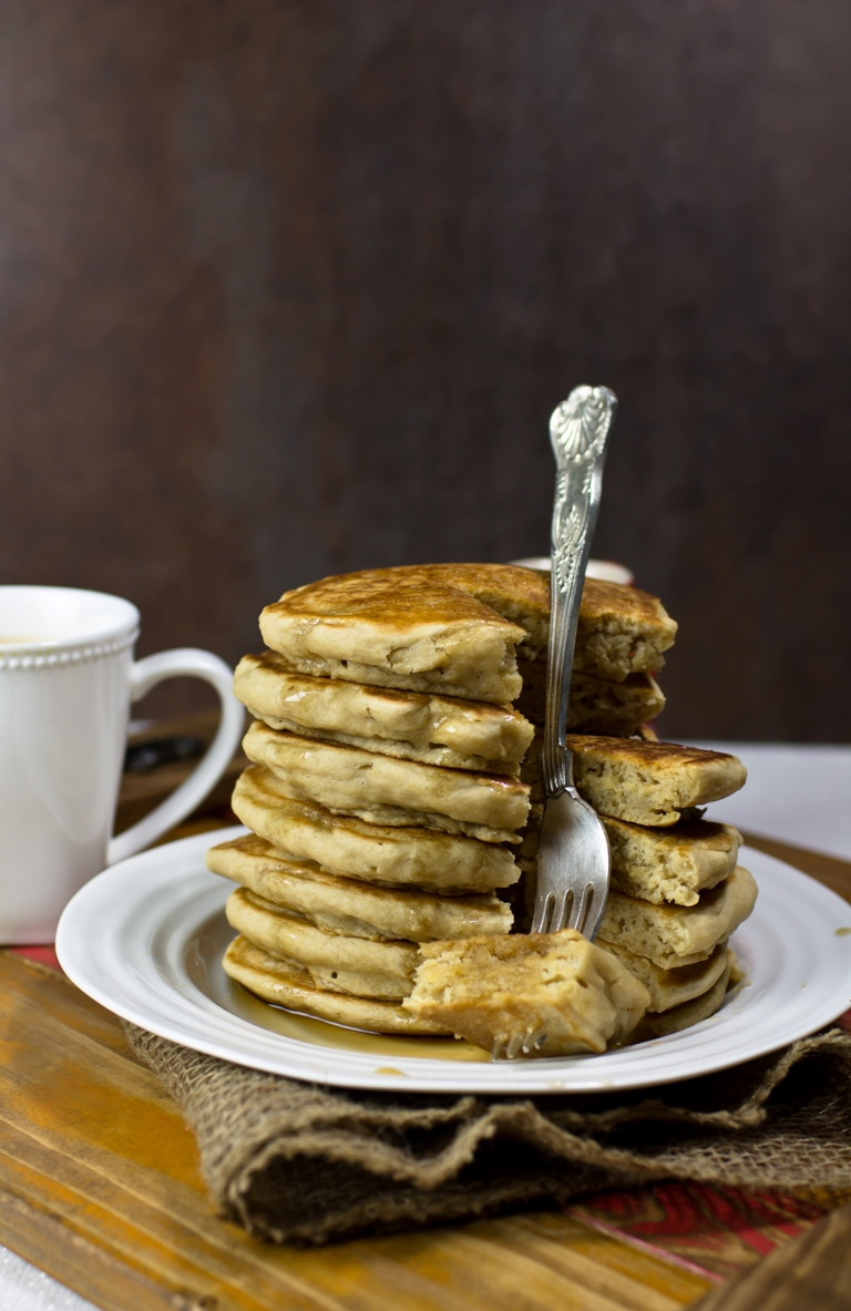 Stack of vegan fluffy pancakes on white plate with fork