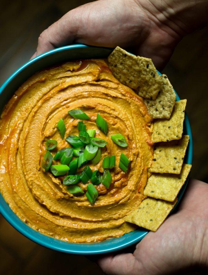 Bowl of Vegan Buffalo hummus with crackers.