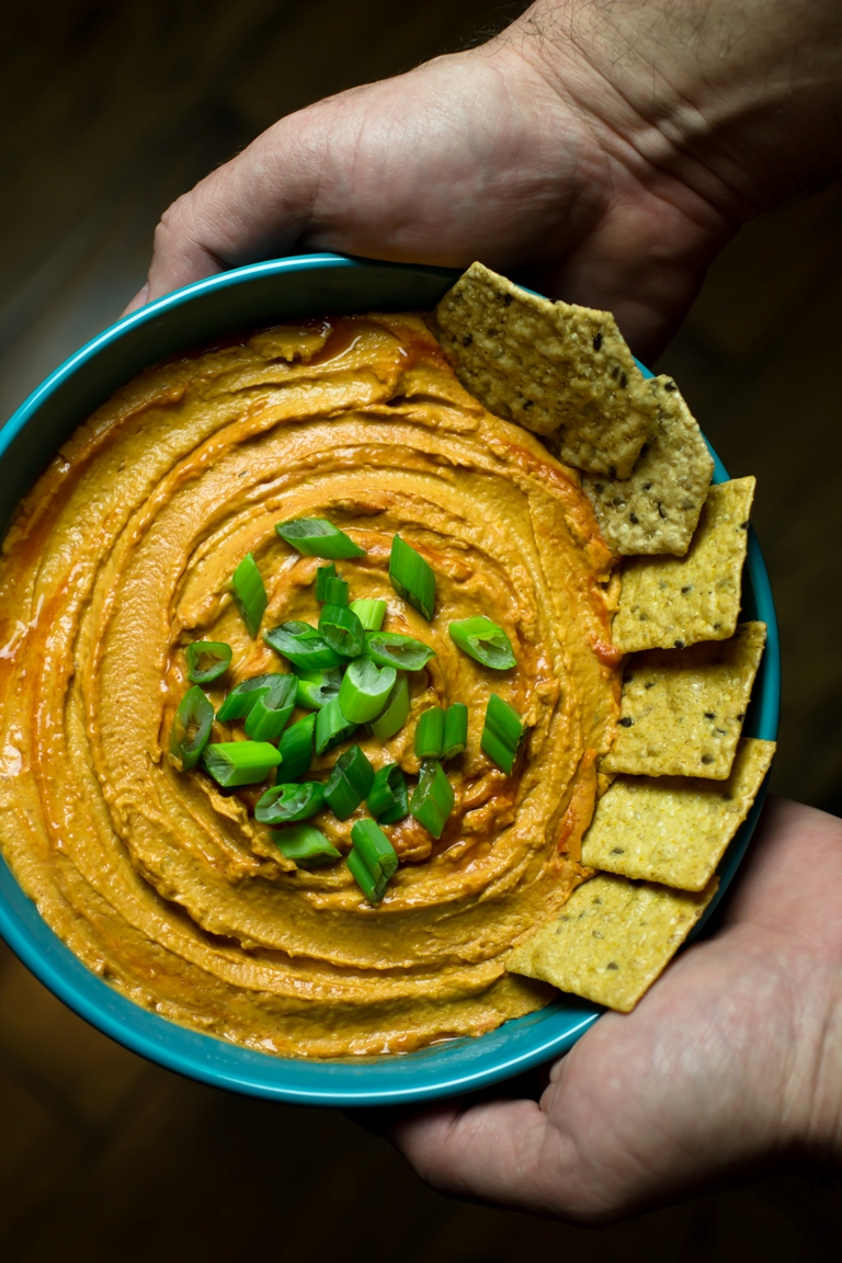 Bowl of Vegan Buffalo hummus with crackers.