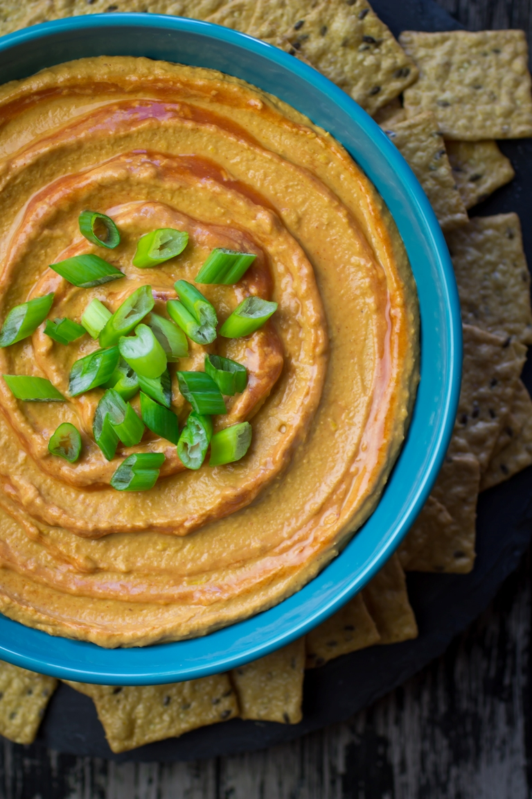 Closeup image of a bowl of spicy vegan buffalo hummus with green onions on top.