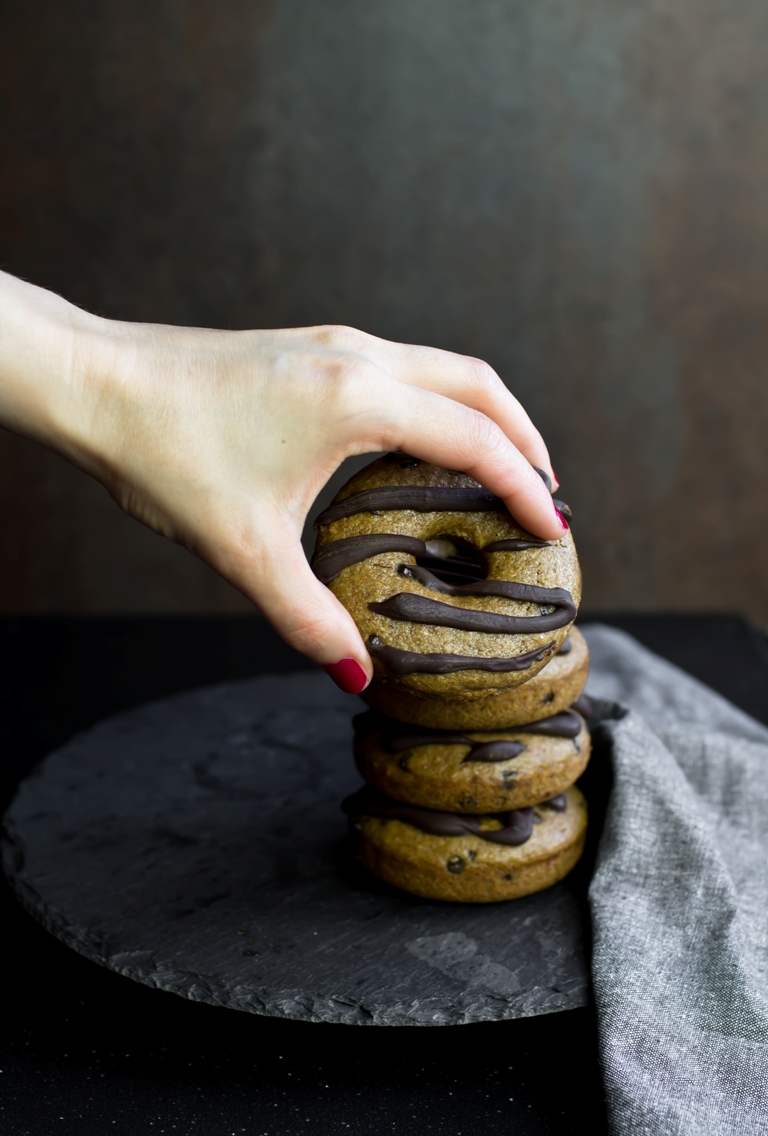 Lady hand grabbing a donut from a stack