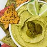 Avocado hummus in bowl with jalapenos
