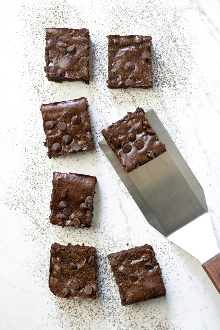8 vegan zucchini brownies with 1 under spatula
