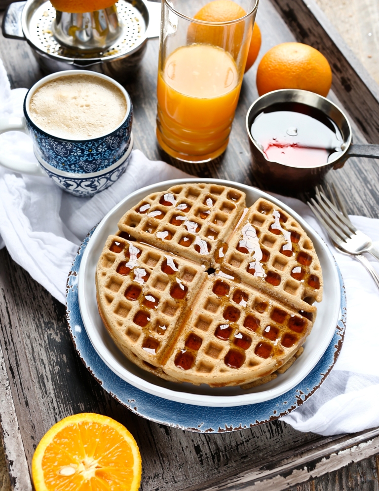 Plate of vegan chai waffles with syrup and orange juice