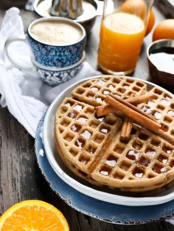plate of chai waffles with cinnamon sticks on top