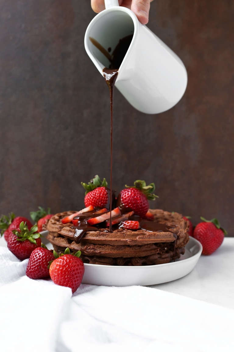 Chocolate syrup pouring over plate of chocolate waffles