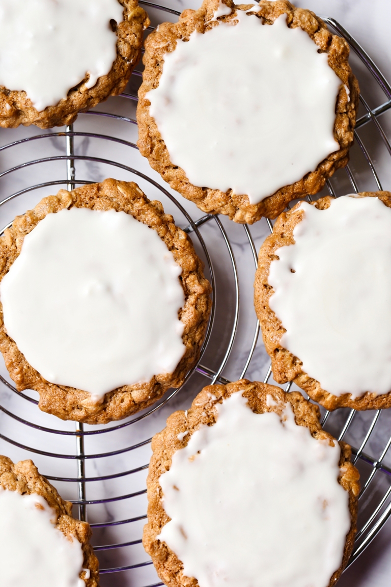 Closeup overhead view of iced oatmeal cookies on round rack