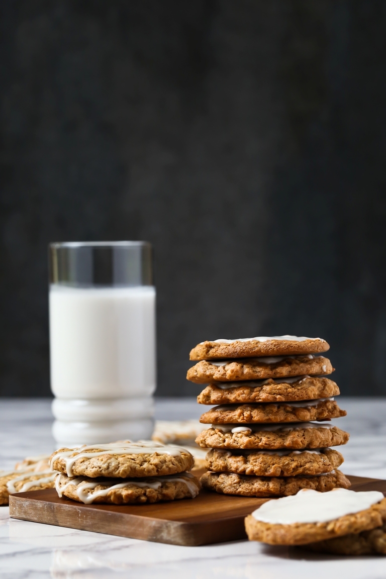 Stack of vegan iced oatmeal cookies on small wooden board