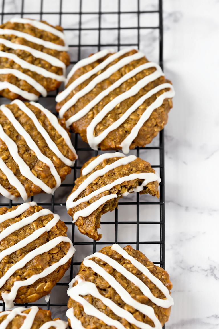 several vegan iced oatmeal cookies with drizzle on cooling rack