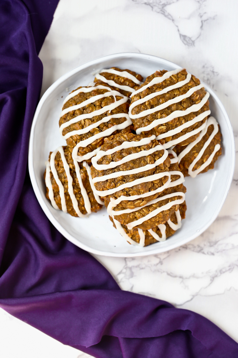 Plate of vegan iced oatmeal cookies with icing drizzled on top