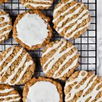 iced oatmeal cookies spread out on cooling rack