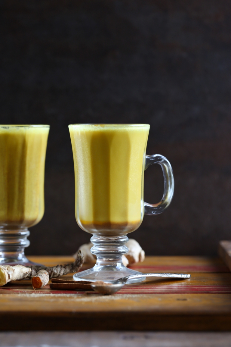 2 glasses of vegan turmeric lattes on wooden tray
