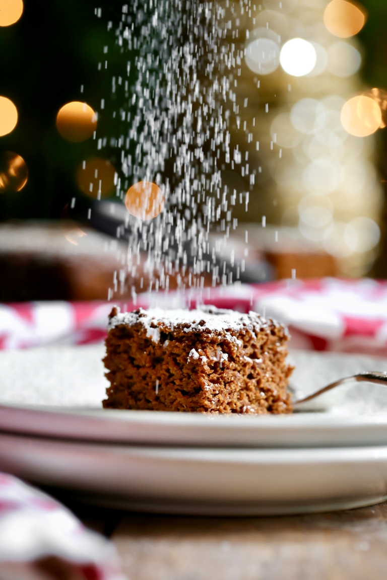 powered sugar falling above onto slice of vegan gingerbread cake