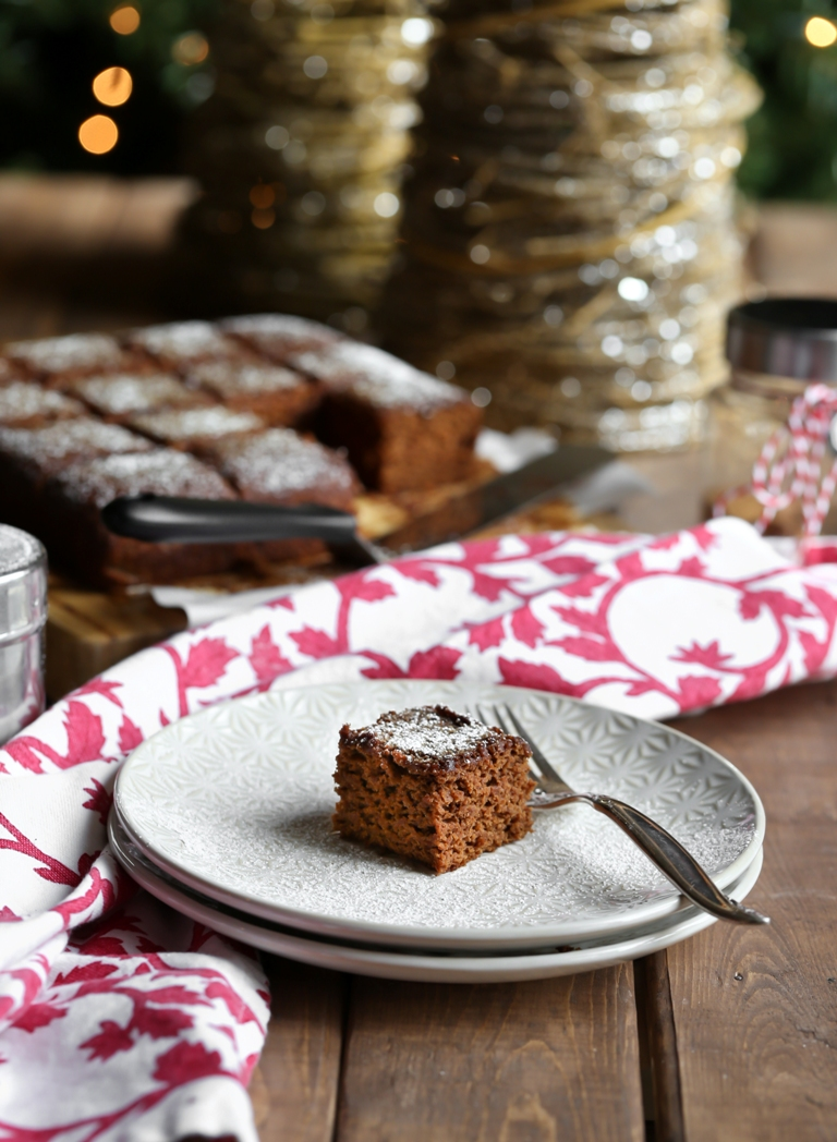 Slice of vegan gingerbread cake on a white plate with fork