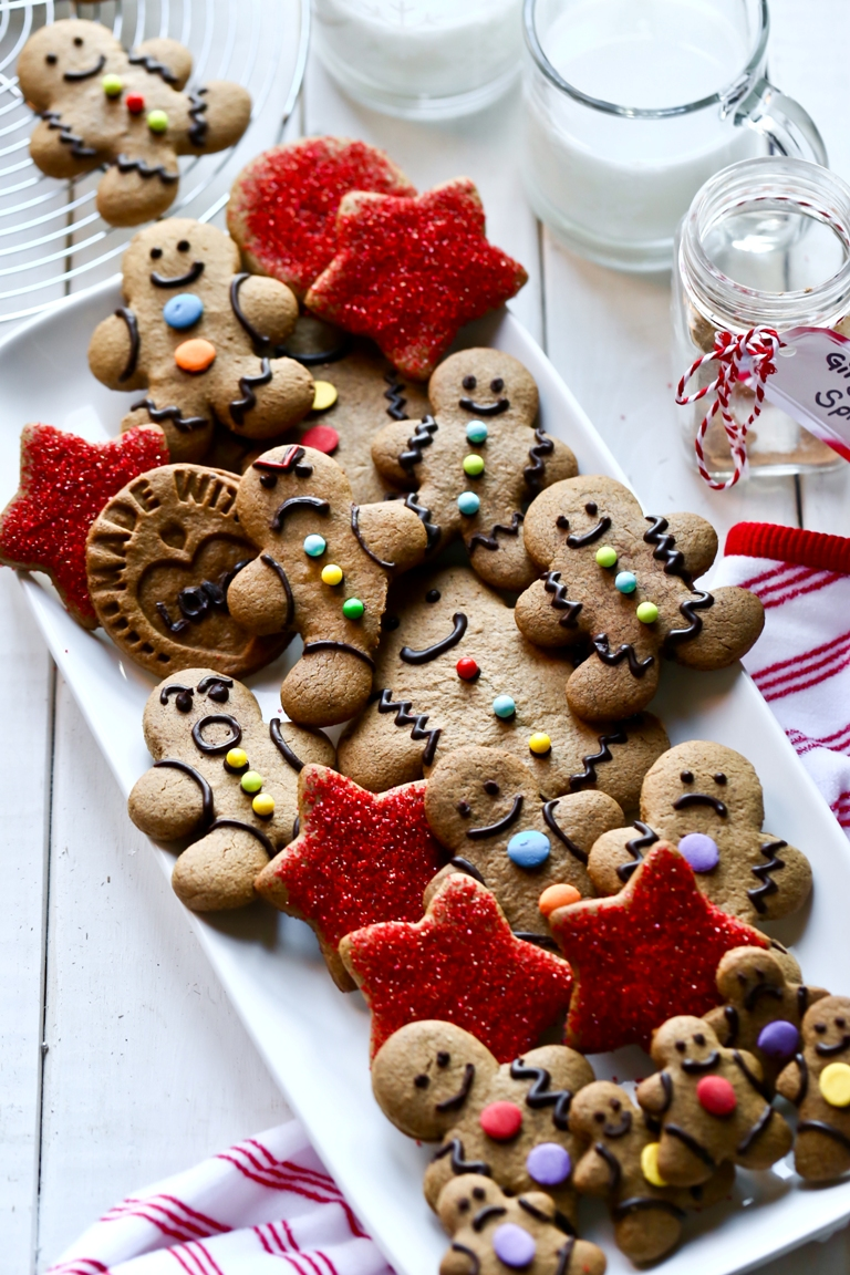 bunch of gingerbread men cookies and red star cookies on large white platter