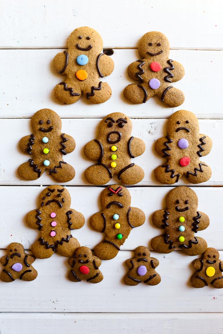 overhead shot of several gingerbread men on white wood
