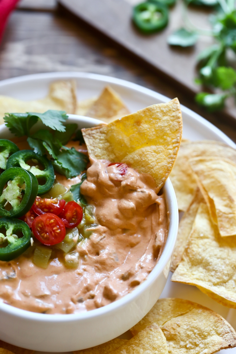 Vegan queso cheese dip in a bowl with chips on the side and jalapenos on top.