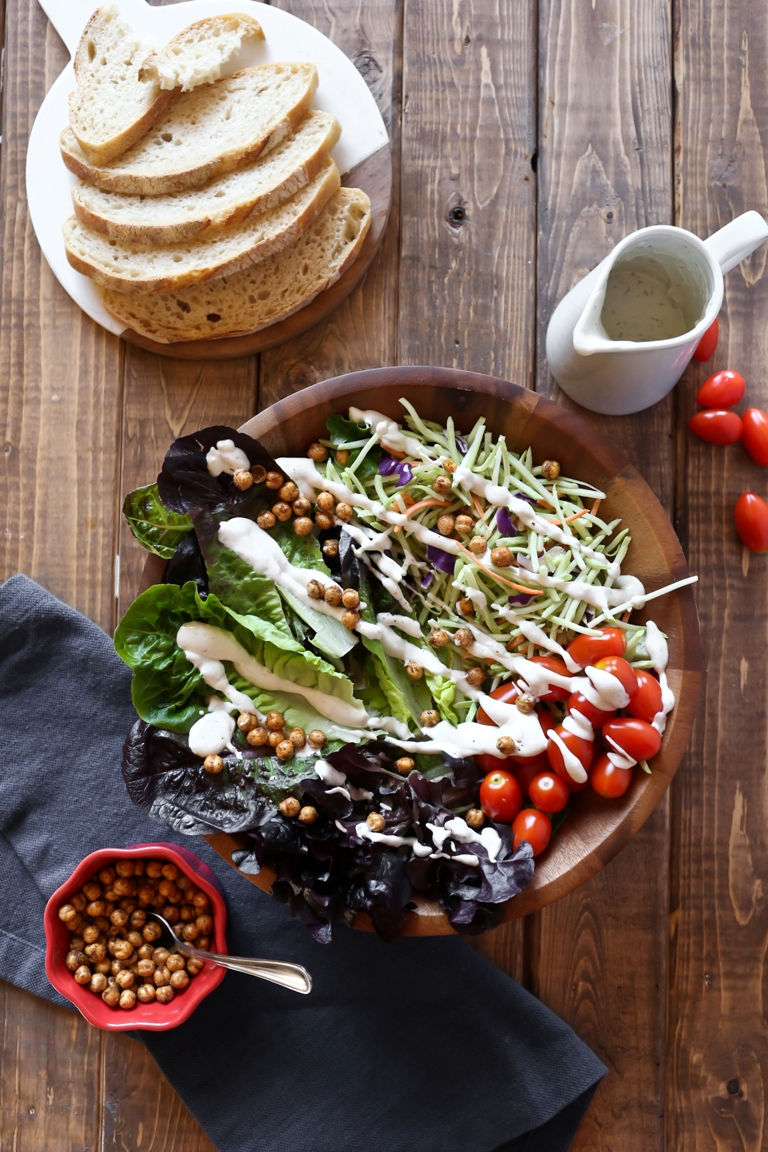 Wooden bowl with a salad and vegan ranch dressing