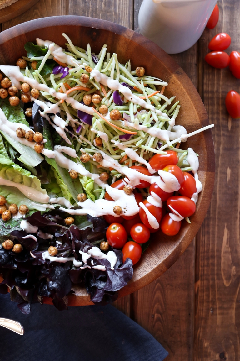 Closeup of a large salad with vegan ranch drizzled on top