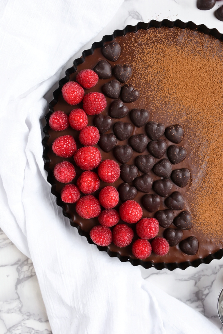Whole vegan chocolate tart with raspberries and chocolate hearts