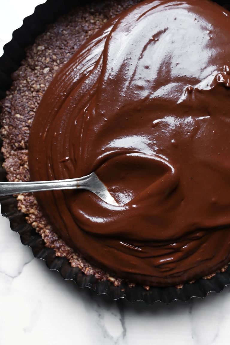 Spoon spreading out melted chocolate on a crust