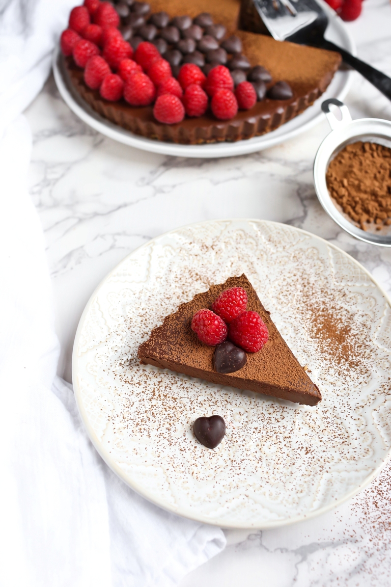 Piece of vegan chocolate sweet potato tart with raspberries