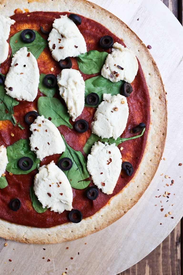 Closeup image of pizza with vegan almond ricotta cheese, spinach and black olives.