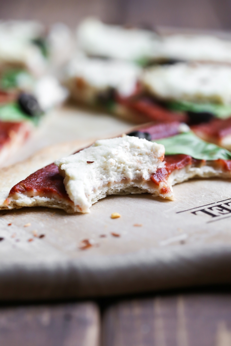 Piece of pizza with a big bite taken out of it showing vegan almond ricotta cheese.