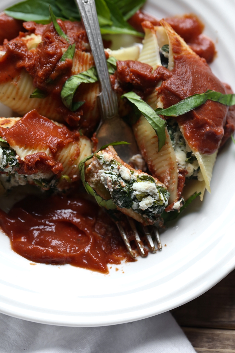 White plate with fork and vegan stuffed ricotta shells and spinach