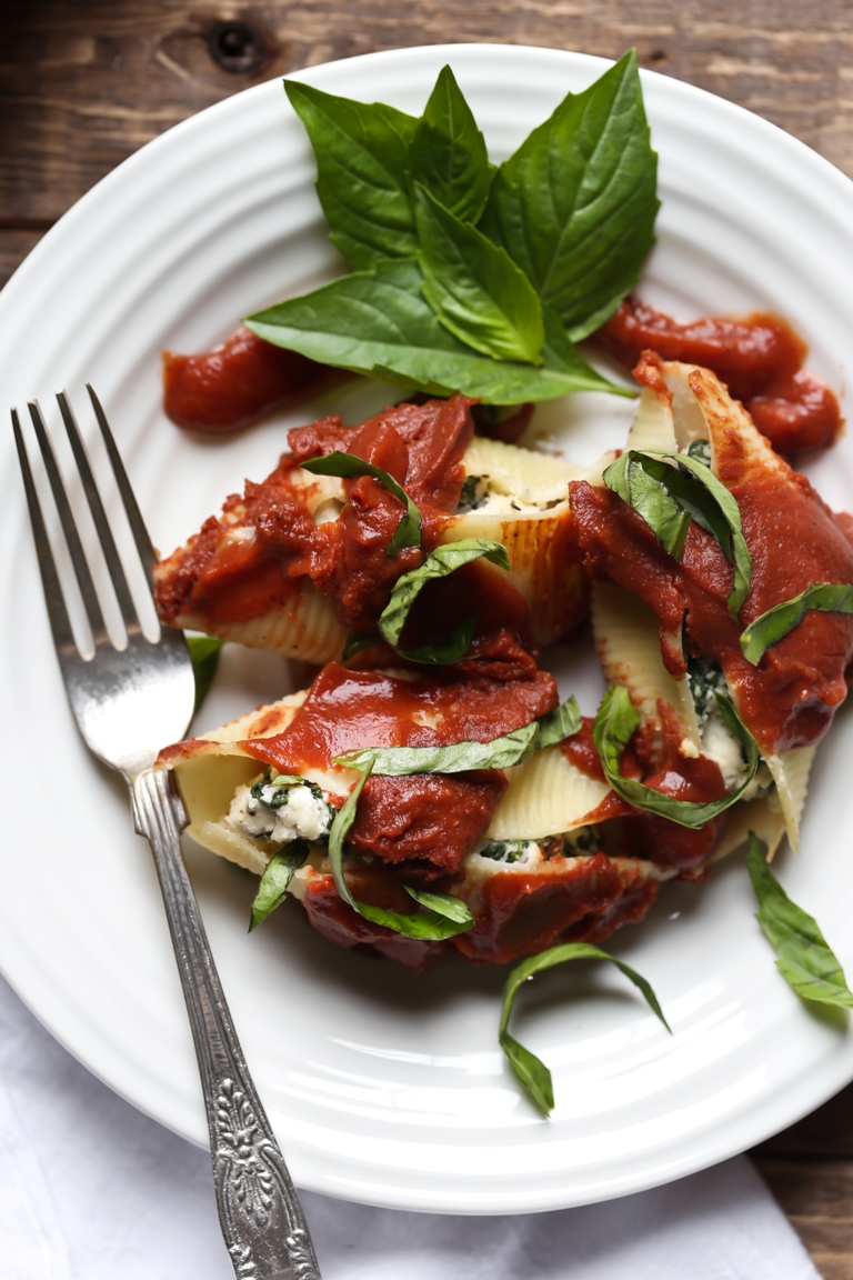 White plate with fork and stuffed ricotta cheese shells with fresh basil