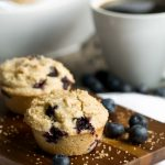 2 vegan blueberry muffins on wood platter