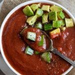 spoon in tomato soup with chopped avocado