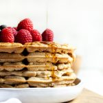 stack of vegan vanilla waffles with syrup pouring above