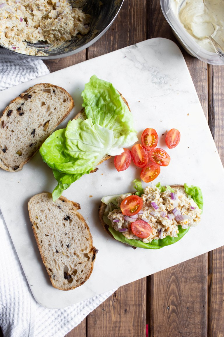 Slices of bread with tomatoes and vegan Caesar chickpeas