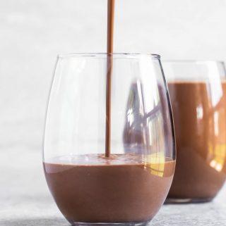 Pouring homemade vegan chocolate milk into glass