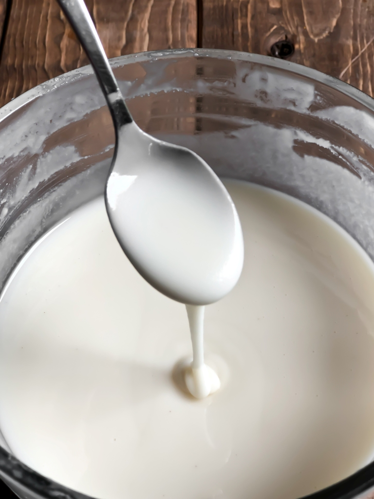 Melted coconut butter dripping off a spoon into a bowl.
