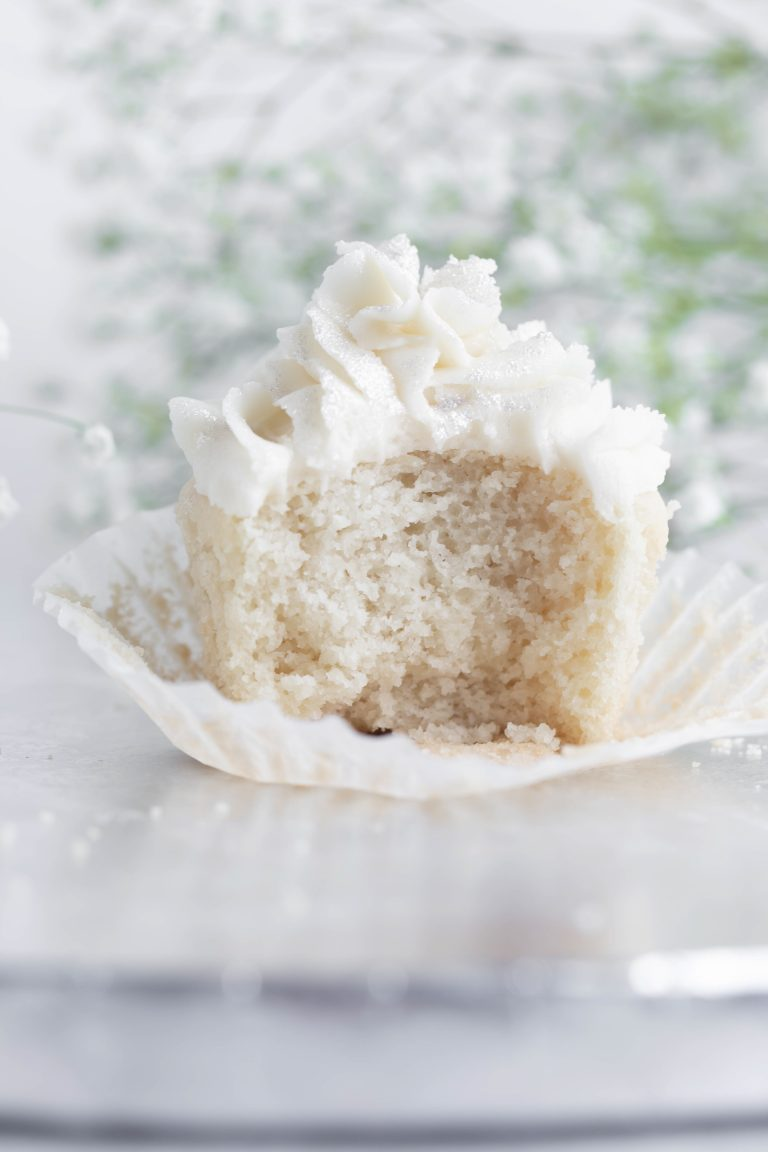 Closeup inside shot of vegan white cupcake showing how fluffy the texture is.