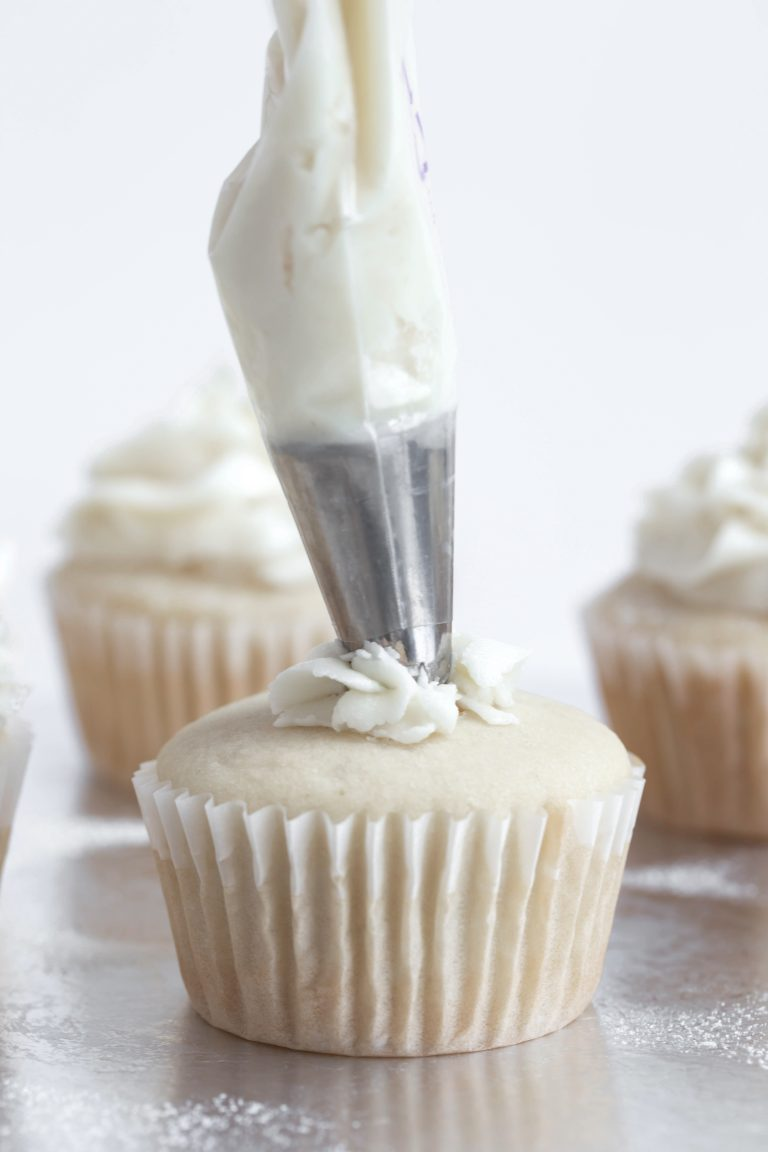 Piping bag with white frosting coming out of the tip onto a white wedding cupcake.
