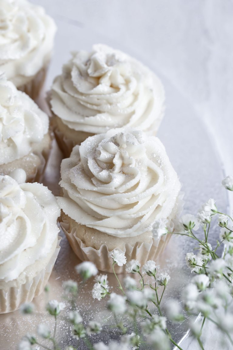 Vegan vanilla wedding cupcakes with white buttercream frosting on a silver platter.